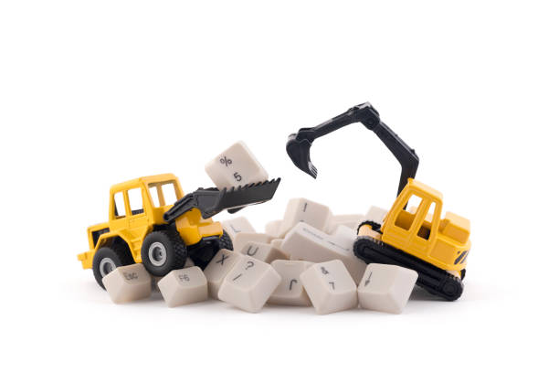 Bulldozer and excavator working on computer keys isolated on white background with clipping path. Website under construction concept. stock photo