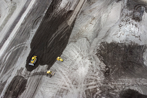 Bulldozer and trucks on a disposal site - aerial view