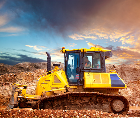 Yellow excavator digging a heap of gravel in forest.