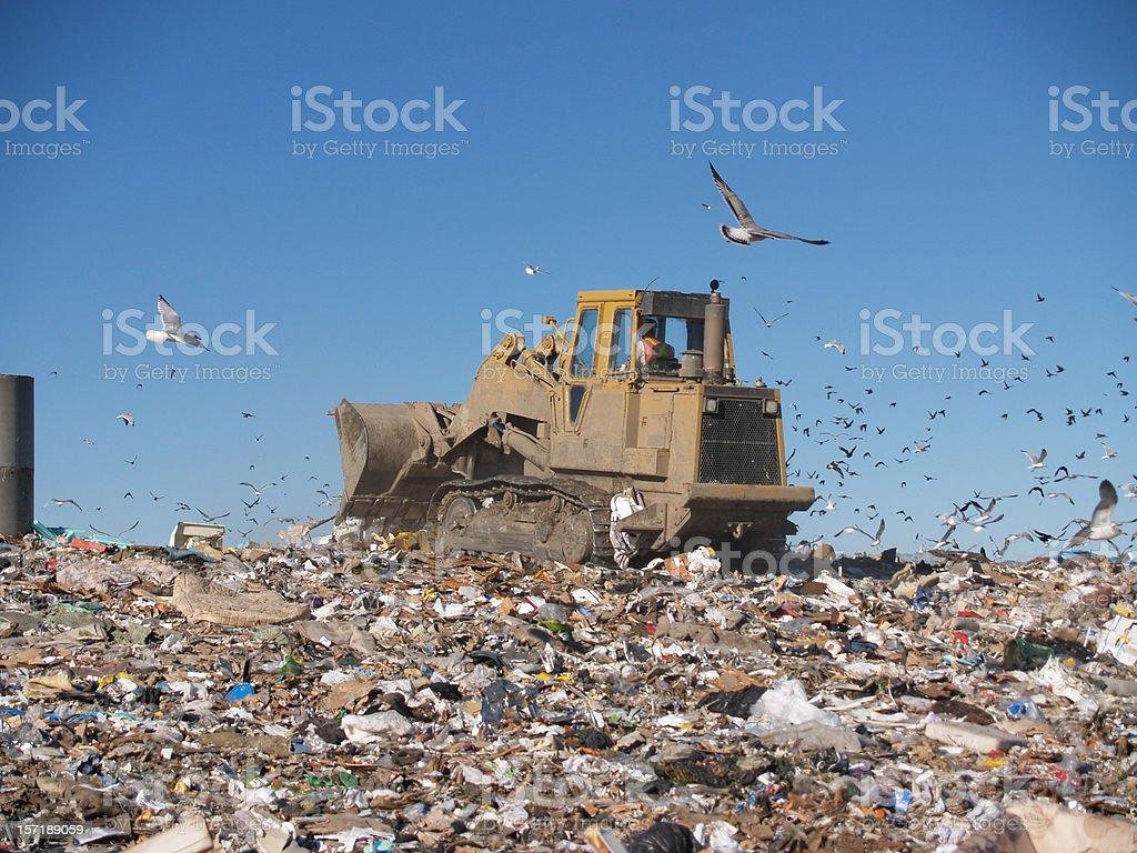 Bulldozer Crushing Trash at Dump royalty-free stock photo