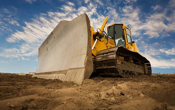 a bulldozer digging up the earth - graven stockfoto's en -beelden