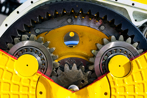 Drive gear and bearings, bulldozer sprocket internal mechanism, large construction machine with bolts and yellow paint coating, heavy industry, detail