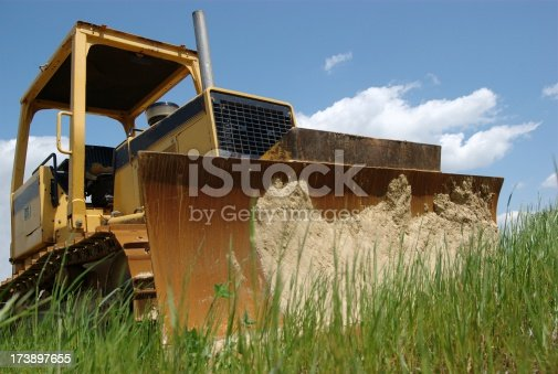 A bulldozer sits in a grass field awaiting its next task.More Images: