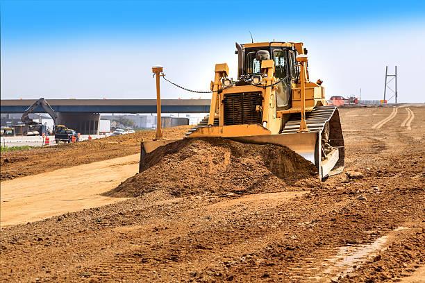 Bulldozer leveling dirt on new road stock photo