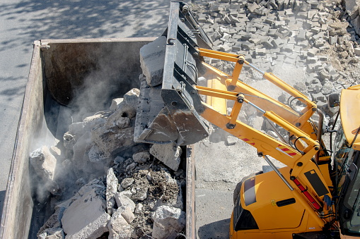Bulldozer loader uploading concrete debris into dump truck at construction site