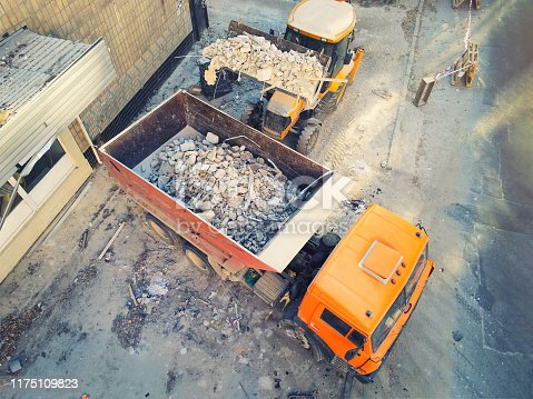 Bulldozer loader uploading waste and debris into dump truck at construction site. building dismantling and construction waste disposal service. Aerial drone industrial background.