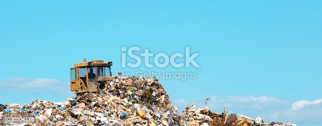 A DSLR photo of landfill with a bulldozer on a blue sky background. Space for copy.
