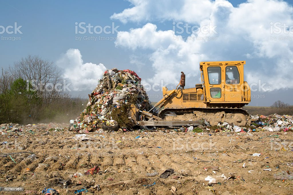 Bulldozer moving garbage in a landfill stock photo