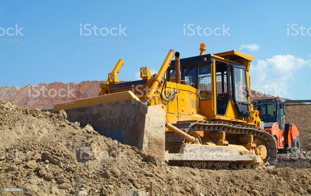 Bulldozer on construction site moving soil stock photo