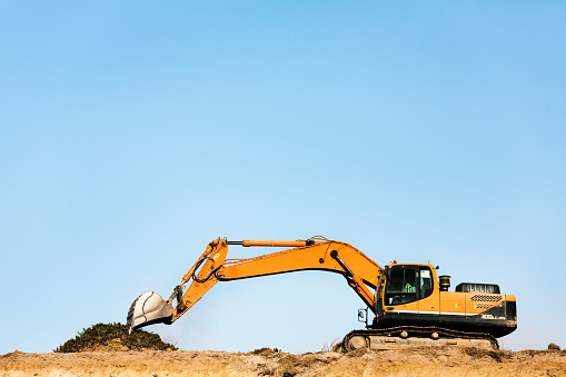 Low angle view of bulldozer on quarry against clear blue sky