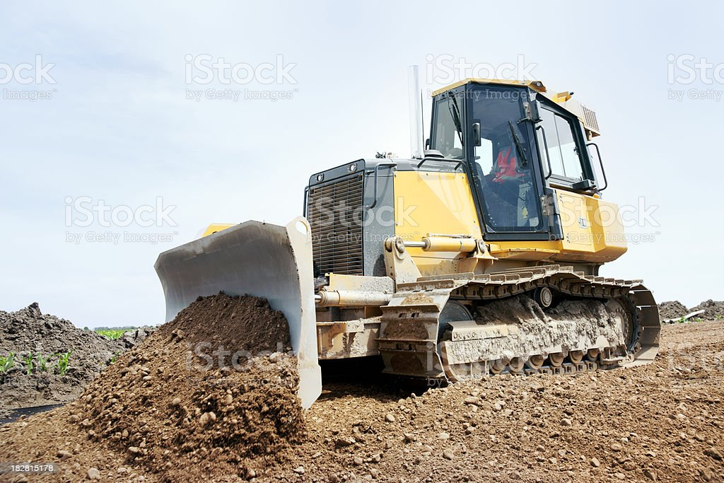 Bulldozer or earthmover machine working on road construction royalty-free stock photo