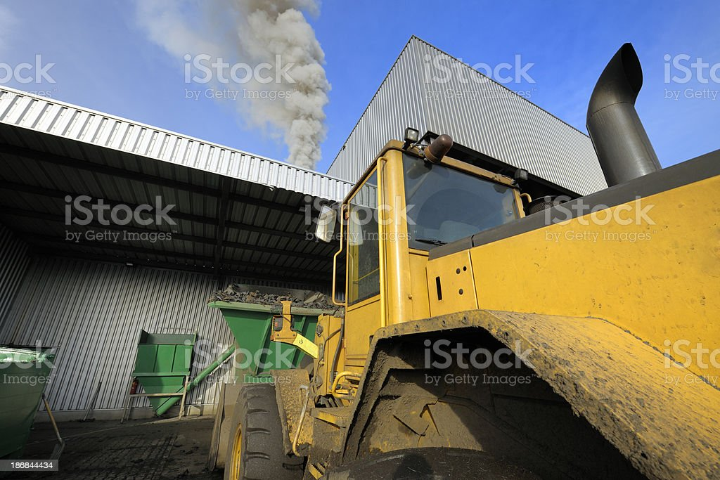 bulldozer parked in front of plant stock photo