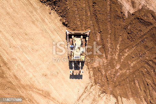 Bulldozer pushing large amount of fresh soil, Aerial image.