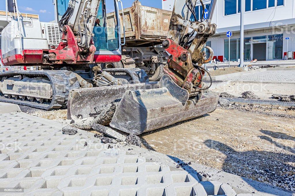 Bulldozer with bucket removes broken asphalt, close up. stock photo