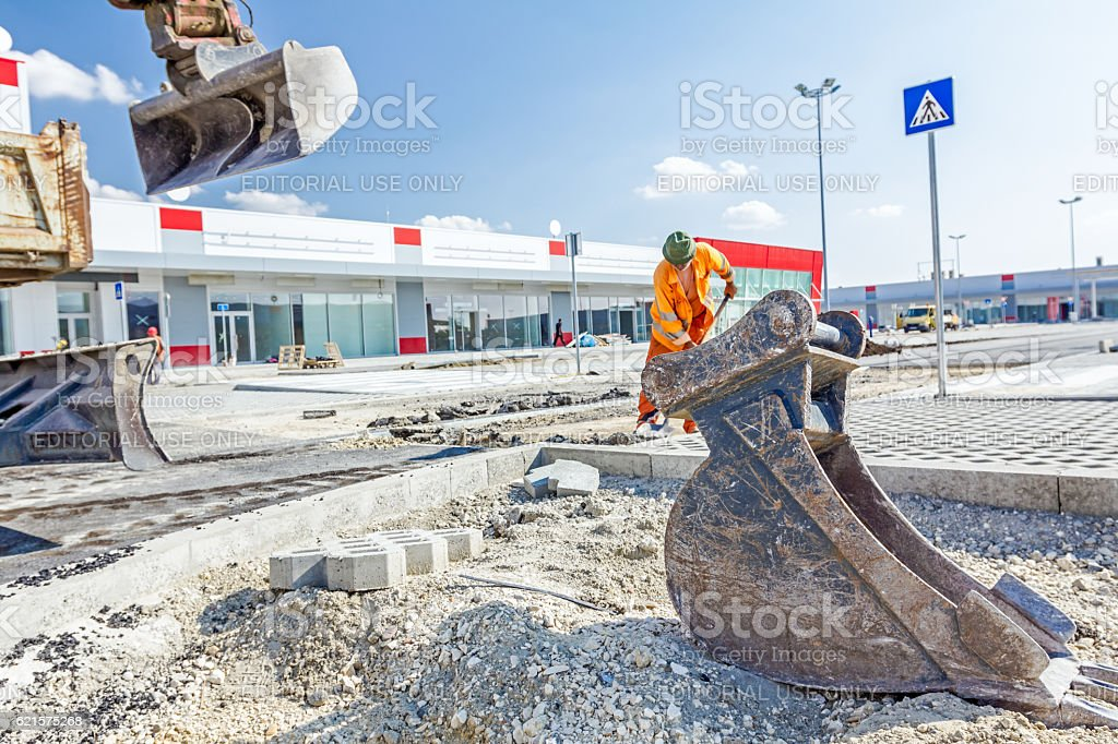 Bulldozer with bucket removes broken asphalt, close up stock photo