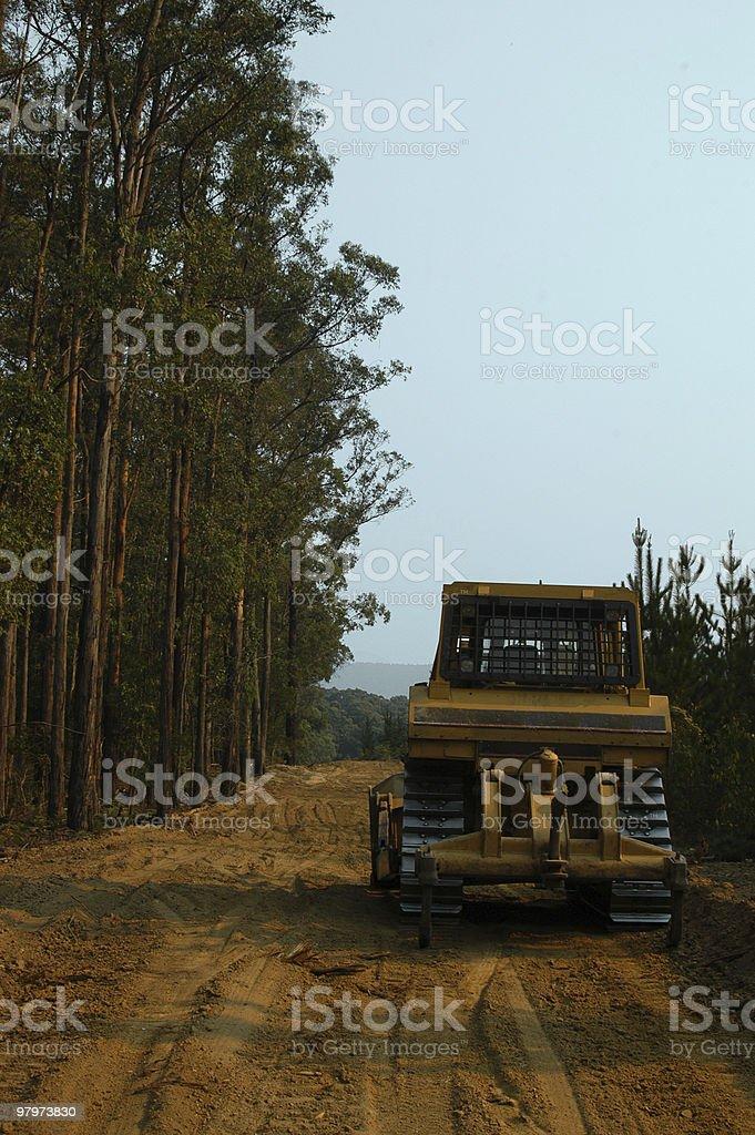 Bulldozer with tall trees royalty-free stock photo