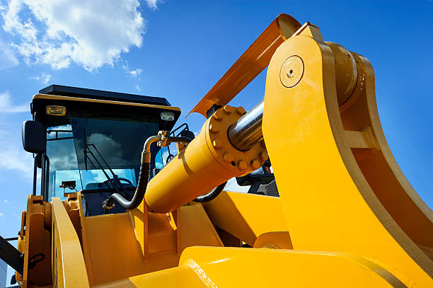 Bulldozer with yellow scoop Bulldozer, huge yellow powerful construction machine with big scoop, focused on hydraulic piston arm, heavy industry, blue sky and white clouds on background construction machinery stock pictures, royalty-free photos & images