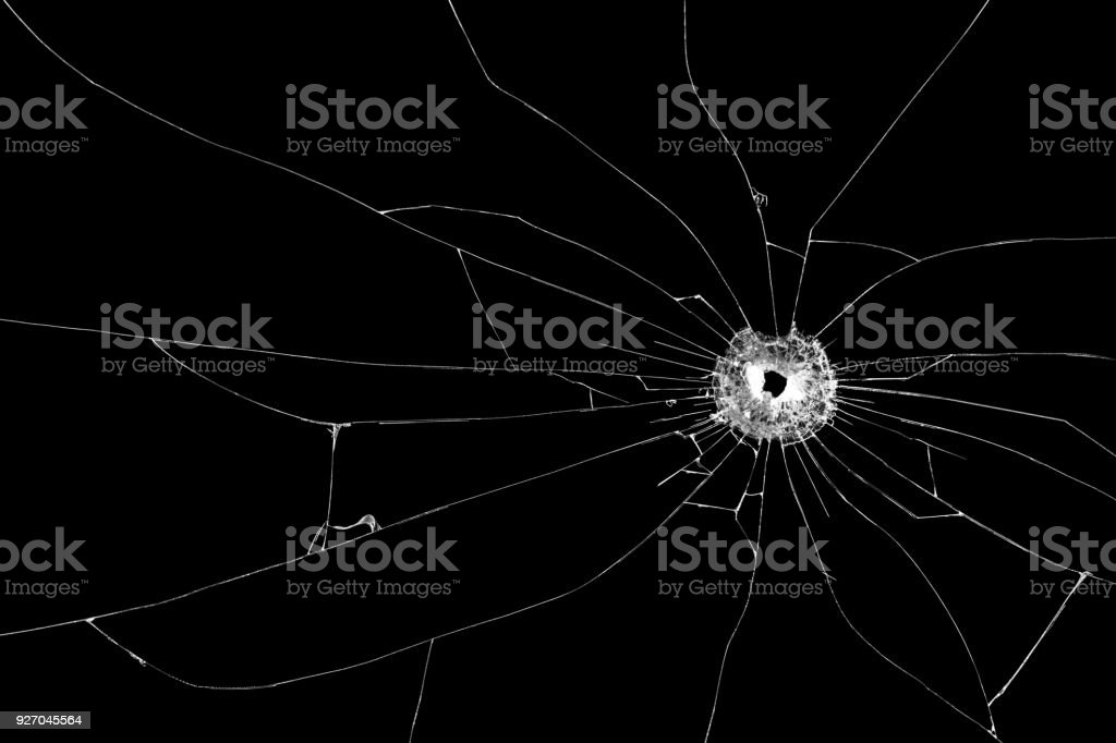 Bullet hole broken glass isolated on black background. Cut out. stock photo