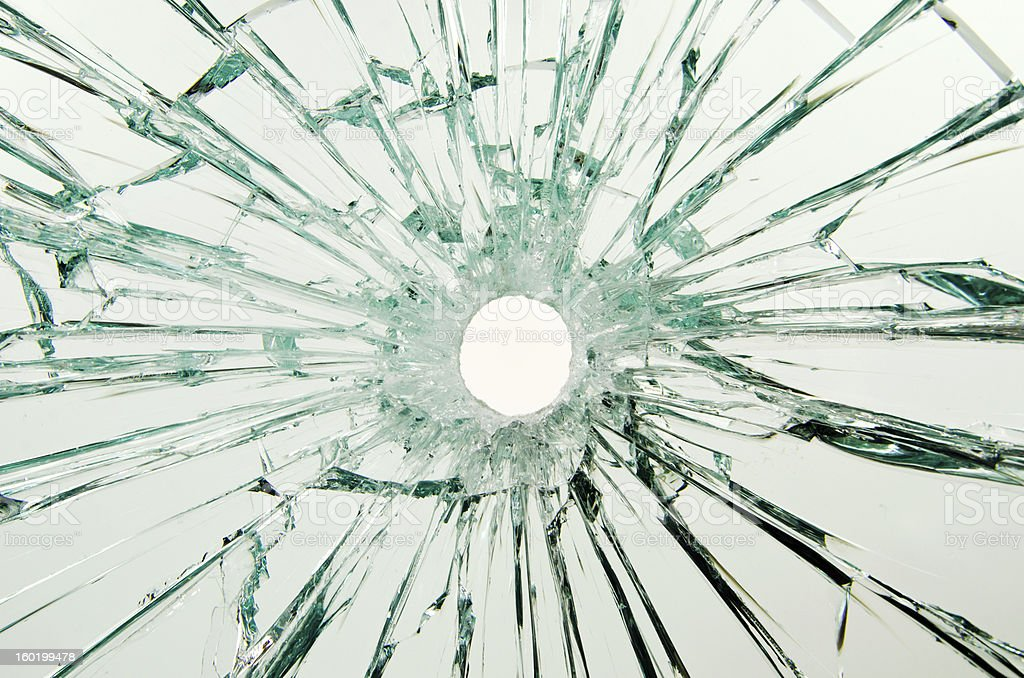 A safety glass car window with a bullet hole through the glass....