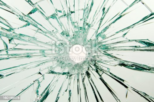 A safety glass car window with a bullet hole through the glass. Close-up. The hole is rough because of the plastic in the glass layers.
