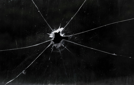 Bullet hole in dirty glass