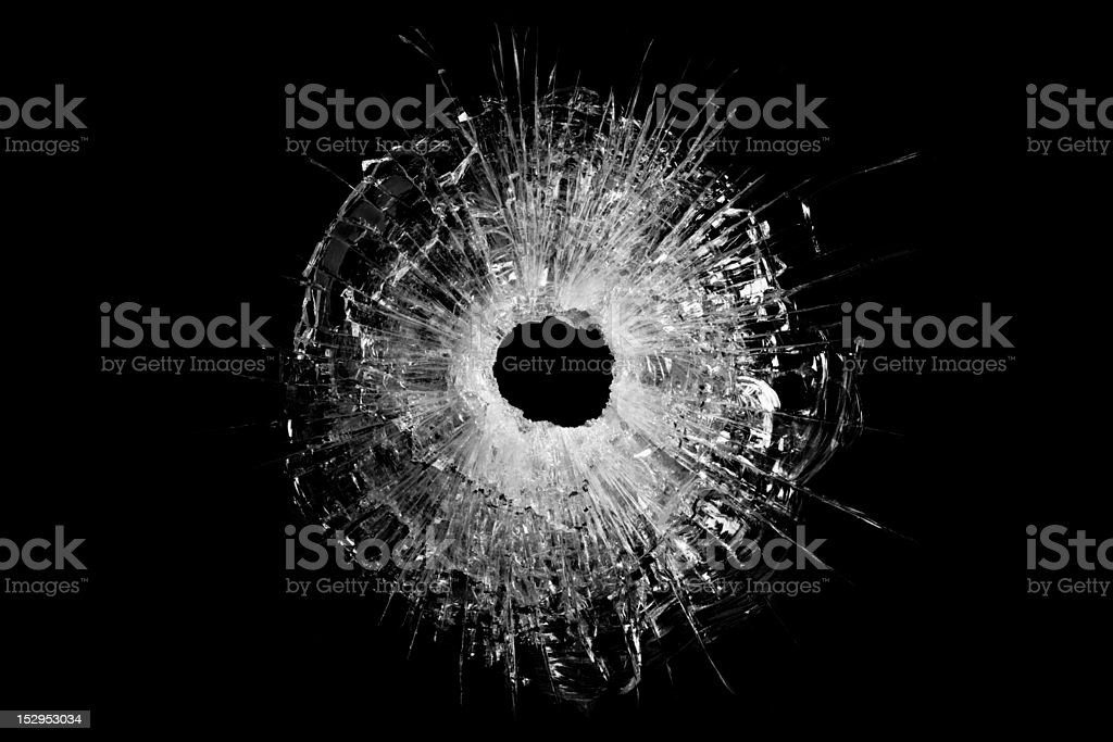 bullet hole in glass closeup and isolated on solid black. Actual...