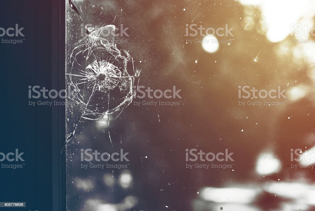 Bullet hole in the window toned stock photo