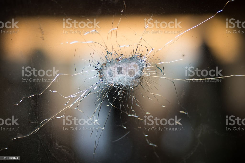 Bullet holes in a front windshield stock photo