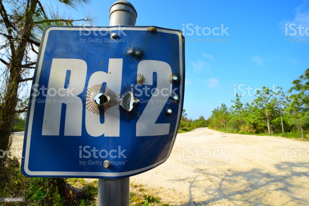 Buracos de bala em nome de estrada de tiro-se Cadastre-se na floresta - Foto de stock de Alumínio royalty-free