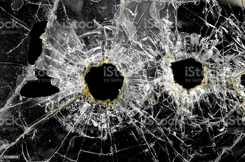 A close-up of two large caliber bullet holes in a windshied... or...