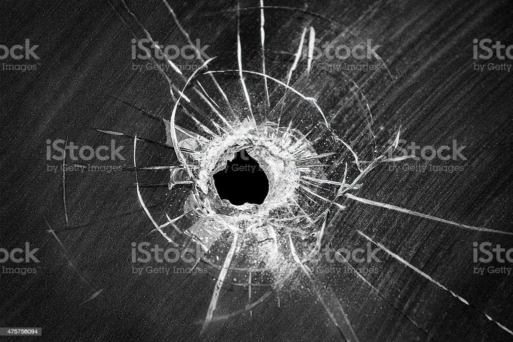 Bullet shot cracked hole on broken window glass stock photo