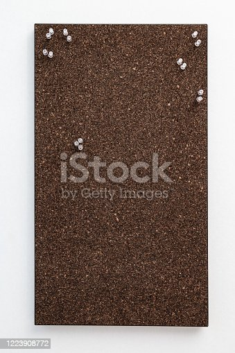 990092558 istock photo Bulletin board from dark brown cork material with transperent pins for stickers. Textured wooden cork closeup as background. 1223908772