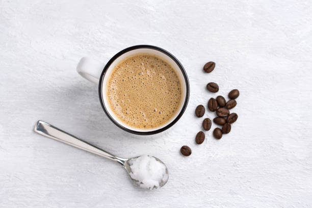 Kugelsicherer Kaffee in weißer Keramiktasse gemischt mit Butter, Kokosöl und Kaffeebohnen. Paläo, ketogene Getränk Frühstück – Foto