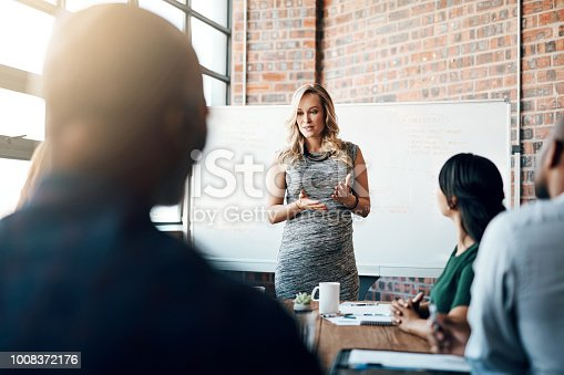 Shot of a pregnant businesswoman giving a presentation in the boardroom