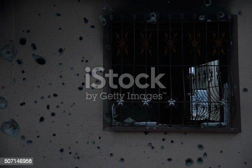 691128564istockphoto Bullet-riddled burned wall 507146958