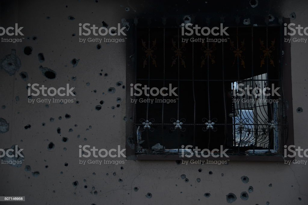 Bullet-riddled burned wall stock photo