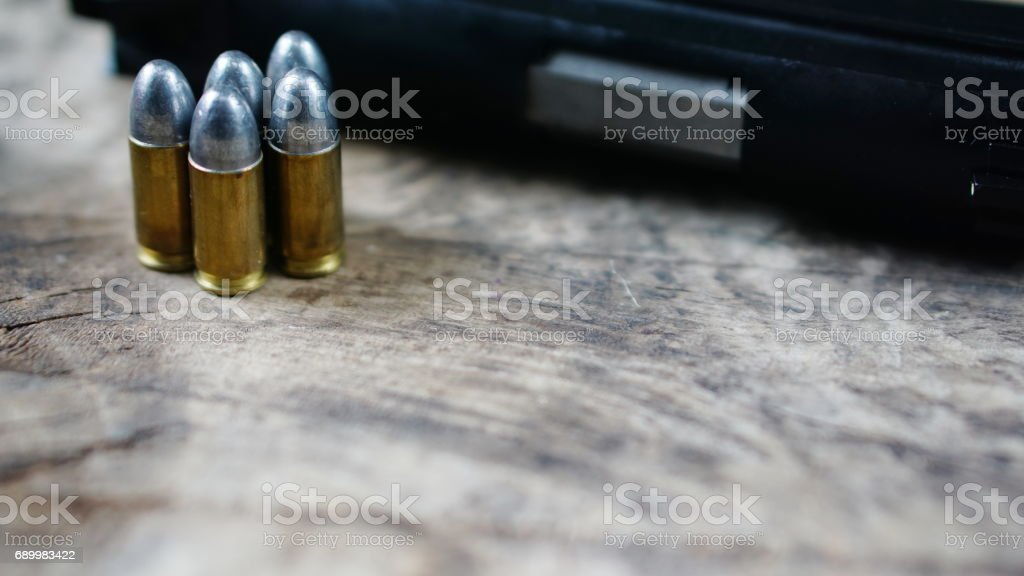 Bullets and a firearm on the wood stock photo