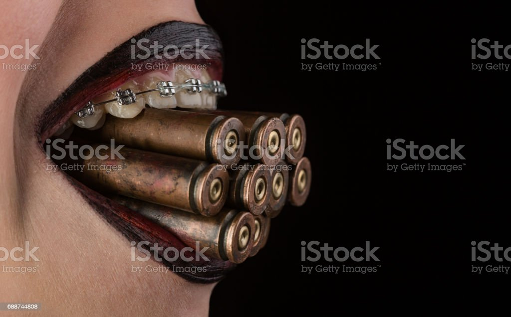 Bullets from revolver or hand pistol between teeth with braces. Dentistry and orthodontics, alignment of teeth as a weapon. Female mouth with bullets with black lipstick on black background stock photo