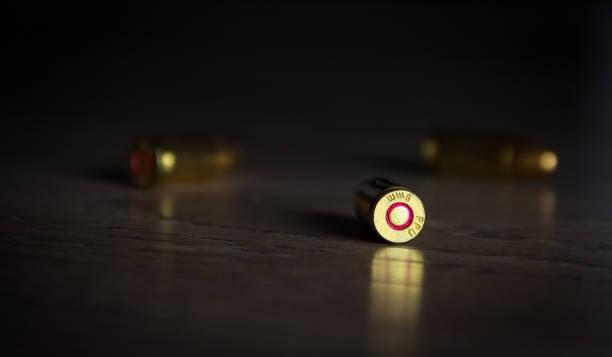 bullets in shadow on floor - proiettile foto e immagini stock