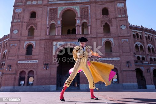 Bullfighter in front of the main gate of bullring Las ventas, Madrid, Spain. Because the bullring facade shown in the picture (Madrid, Las Ventas Bullring) is owned by the municipality of Madrid, images taken of the exterior building are of public domain, therefore a property model release is not necessary. Also, the Las Ventas Bullring, is not linked to any particular bullfighter, nor private companies.