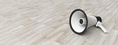 istock Bullhorn, megaphone white with black details on grey wooden floor background, front view, banner, copy space. 3d illustration 1054945522