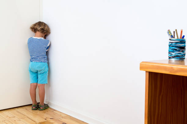 Bullied child Child in naughty corner, being bullied, having time out or having a tantrum. punishment stock pictures, royalty-free photos & images