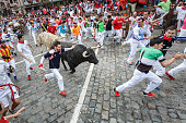 Pamplona, Spain - July 11, 2017: Bulls and people running on the street during the festival of San Fermin. Bulls of the cattle ranch of Jandilla in the fourth run of the festival of San Fermin