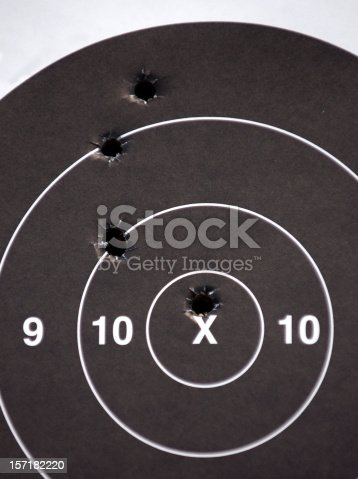 A paper target marked with real bullet holes, one clearly in the bullseye ring.