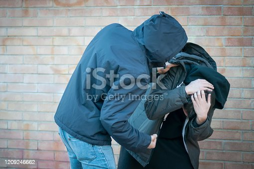 Bullying, aggression and violence scene between two males, one young adult male punches his peer near a bricks wall