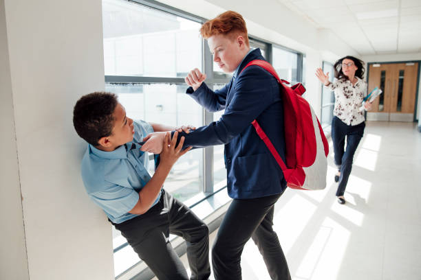Bullying at School Redhead teenage male bullying mixed race teenage boy in the corridor at school. cruel stock pictures, royalty-free photos & images