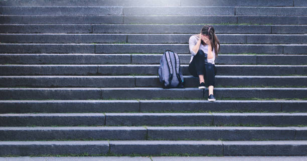bullying, discrimination or stress concept. sad teenager crying in school yard. upset young female student having anxiety. upset victim of abuse or harassment sitting on stairs outdoors. - disbarment stock pictures, royalty-free photos & images