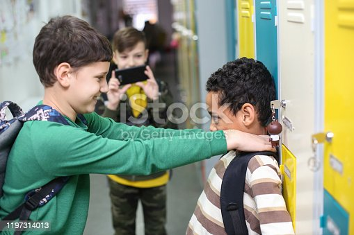 Boys bullying in a school hallway. All about 9-10 years old males.