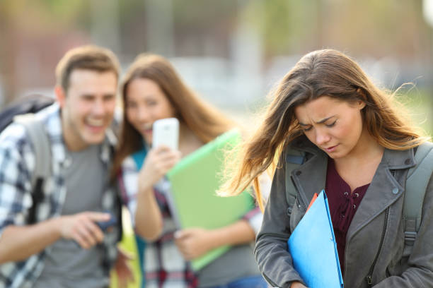 Bullying victim being recorded by classmates Bullying victim being video recorded on a smartphone by classmates in the street with a unfocused background low self esteem stock pictures, royalty-free photos & images