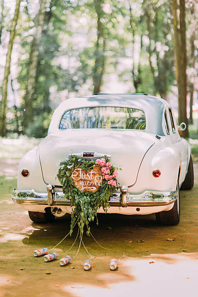 bumper of retro car with just married sign and cans - pas getrouwd stockfoto's en -beelden